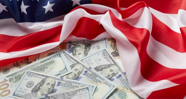 Several one hundred dollar bills arranged on top of an American flag