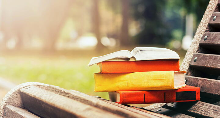 Stack of books sitting on a bench with rays of sun shining down on them