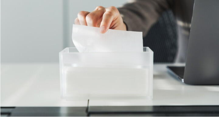 Sick worker at desk taking tissue out of box