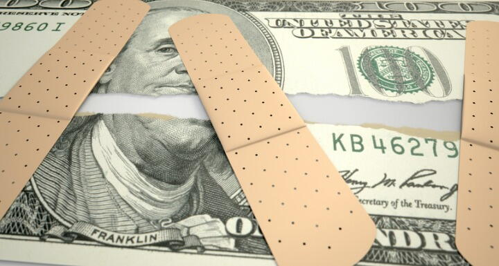 Torn money with bandaids over ripped pieces