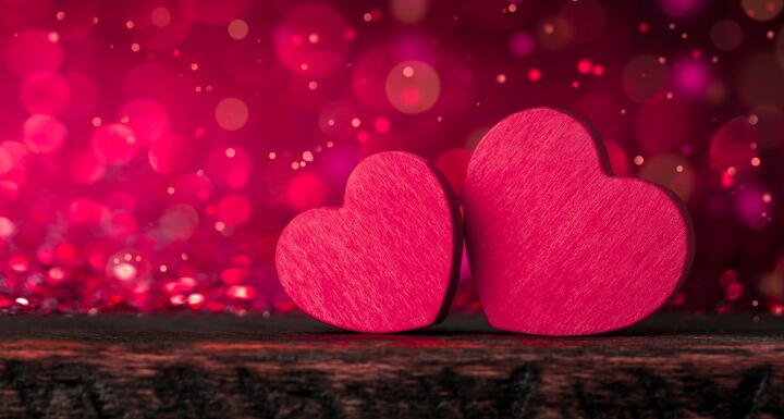 Two pink wooden hearts sitting on a brown wooden table with pink glitter falling in the background