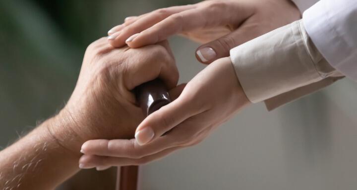 Woman caregiver hands holding elderly patient hand