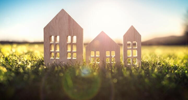 wood model house in empty field at sunset