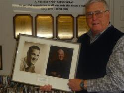 Pete Madsen holds portraits of his old friend and the Vass Area