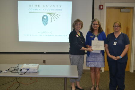Ashe County Community Foundation Grants Chair Karen Powell presents a grant award to Second Harvest Food Bank of Northwestern North Carolina staff.