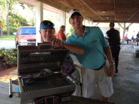 Jay Renfrow, winner of the stainless steel grill, pictured (left) with event co-chair Cory Lewis.