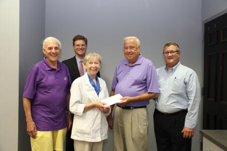Board members Wilson Cox, Mikeal Basinger, Dargan Moore and Larry Aiken (left to right) present a grant award to Marilyn Green of the Helping Hand Clinic.