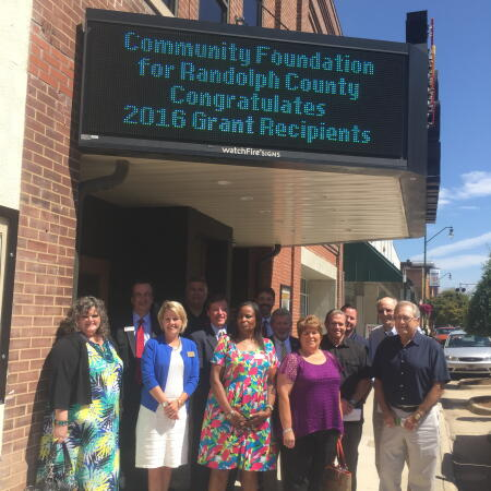 Representatives from grantee partners with board members (L-R) Chris Griffin, Mark Hensley, Darwin Smith, Wayne Thomas and Kevin Franklin in front of the historic Sunset Theater in Asheboro.
