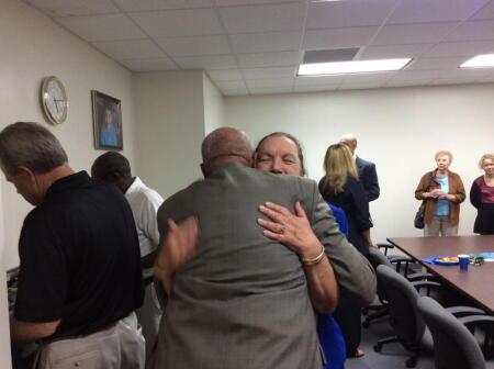 Founding Board Member and Sitting Secretary Gayle Fernandez hugging Founding Board Member John Staton.