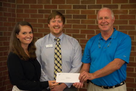 Francis (middle) and Huffman (right) present a grant award to a representative (left) of a nonprofit serving the Unifour area community.
