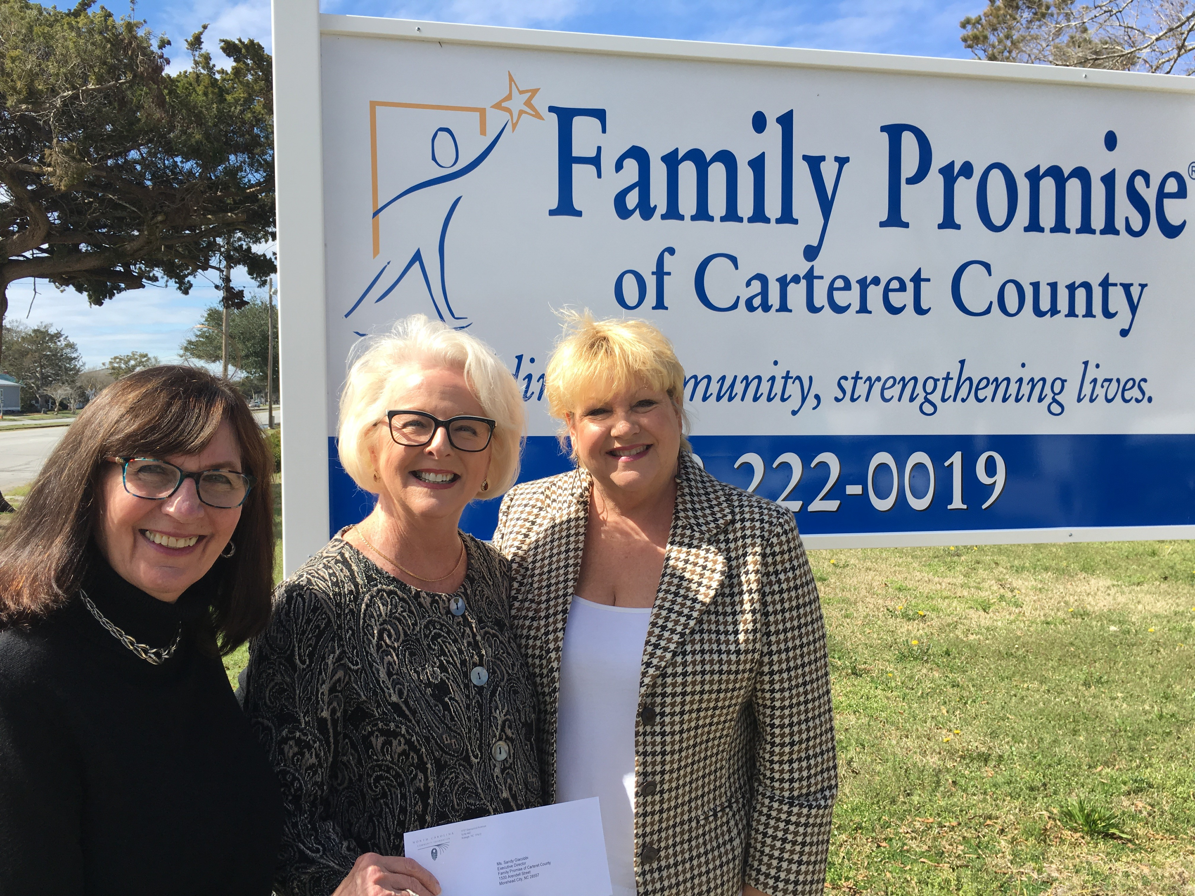 Kniffy Hamilton, CCF board member, and Terry Robertson, CCF board president, present a check to Family Promise of Carteret County to support disaster recovery.