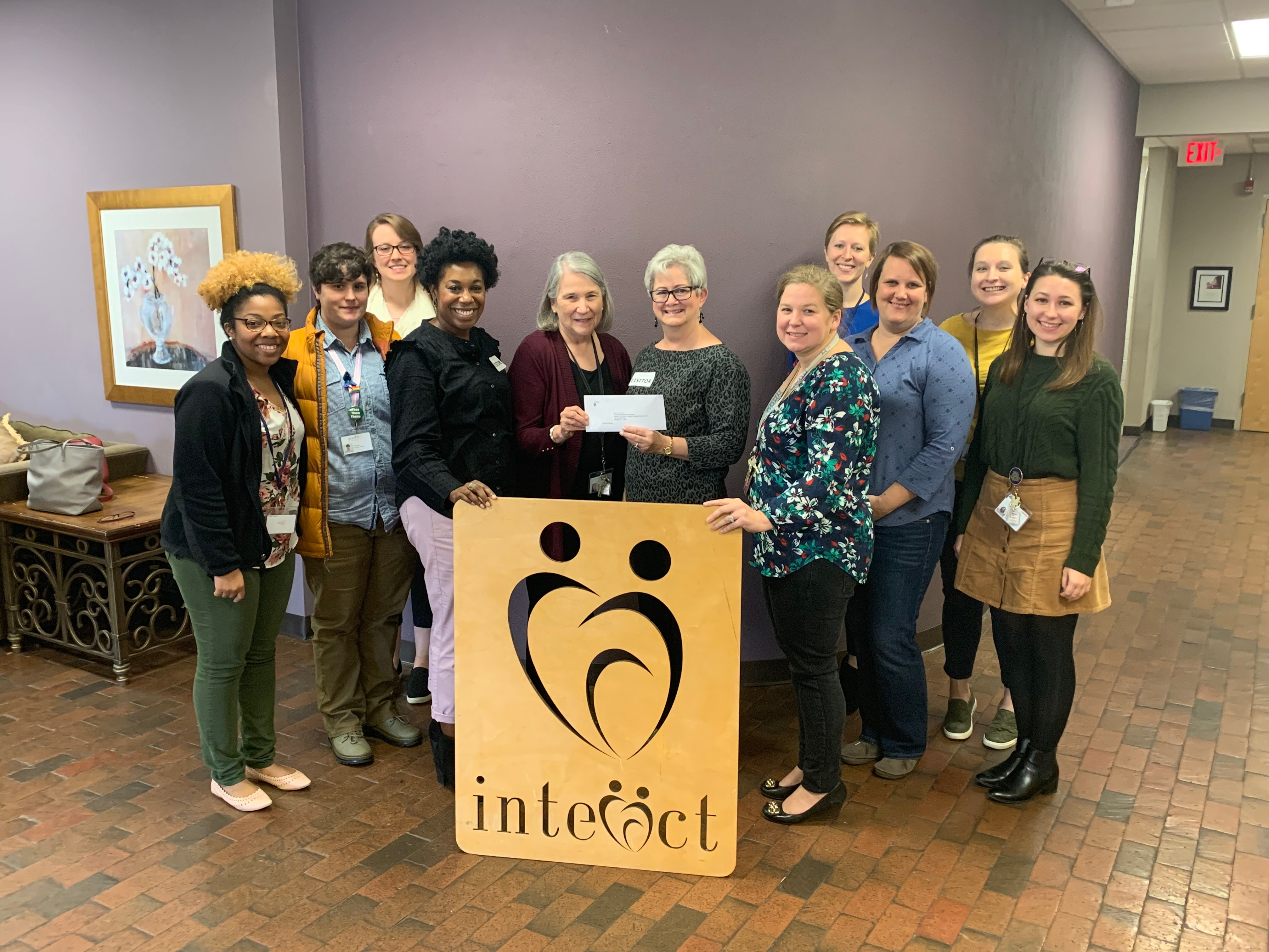 Quinn Novels, NCCF regional director, presents a grant award from the Women's Fund of North Carolina to the staff of InterAct.