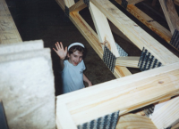 Heather's sister, Crystal, waving from the framed basement of her new Habitat home.