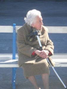 Senior woman with cane sitting on bench