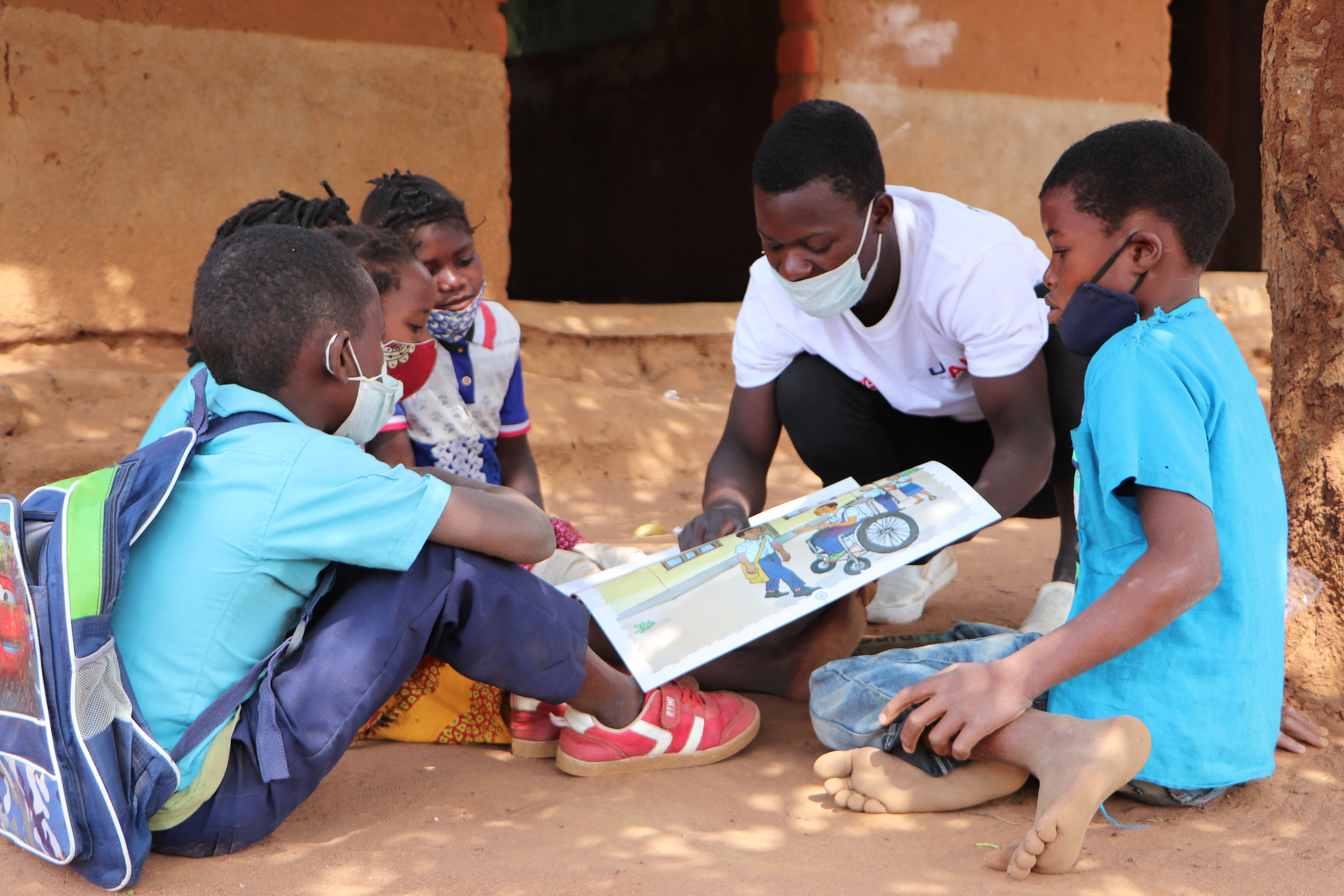 Young male teacher showing book to students in Mozambiue