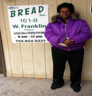 A local woman displays her new coat from Planet Aid and BREAD Ministries
