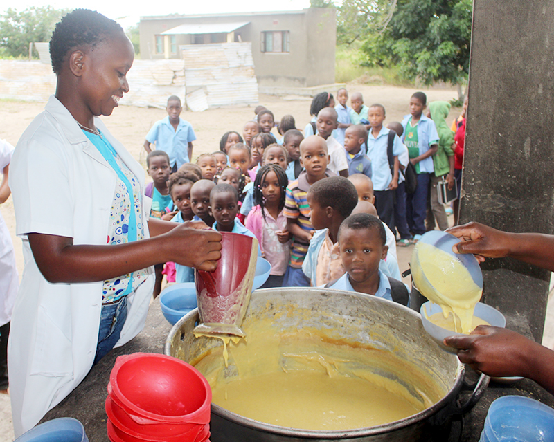 Volunteers dish out corn-soy porridge to students for lunch.