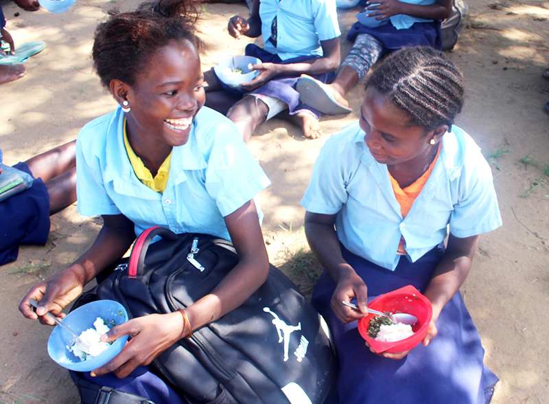Two Mozambican primary-school girls enjoy a lunch of home-grown food.