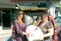 Planet Aid's Megan Singleton donates clothes to Joan Williams of Duplin County's Optimist Club