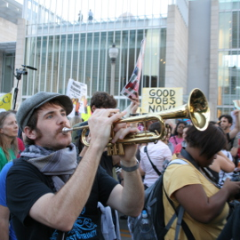 IWJ Organizer Joe Hopkins, plays his trumpet at a Take Back Chicago march