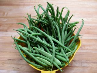 Fresh, uncut green beans in a basket on a wooden counter top