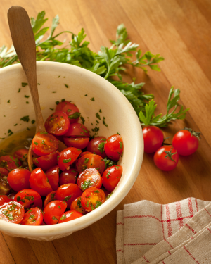 sliced cherry tomatoes with olive oil and chopped basil in a white bowl
