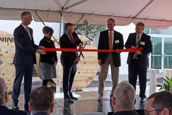 Clark Kinlin, Corning Executive Vice President, flanked by Newton Mayor Anne P. Stedman and Catawba County Board of Commissioners Chair C. Randall Isenhower, cuts the ribbon at Corning's Newton Facility.