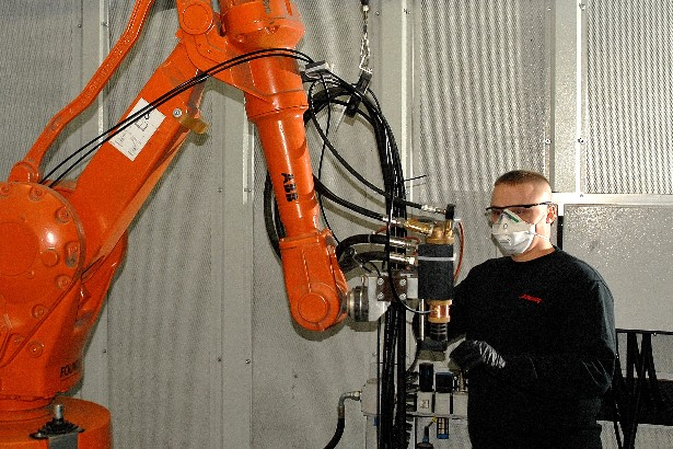 A local manufacturing employee works with robotics equipment at Turbocoating.
