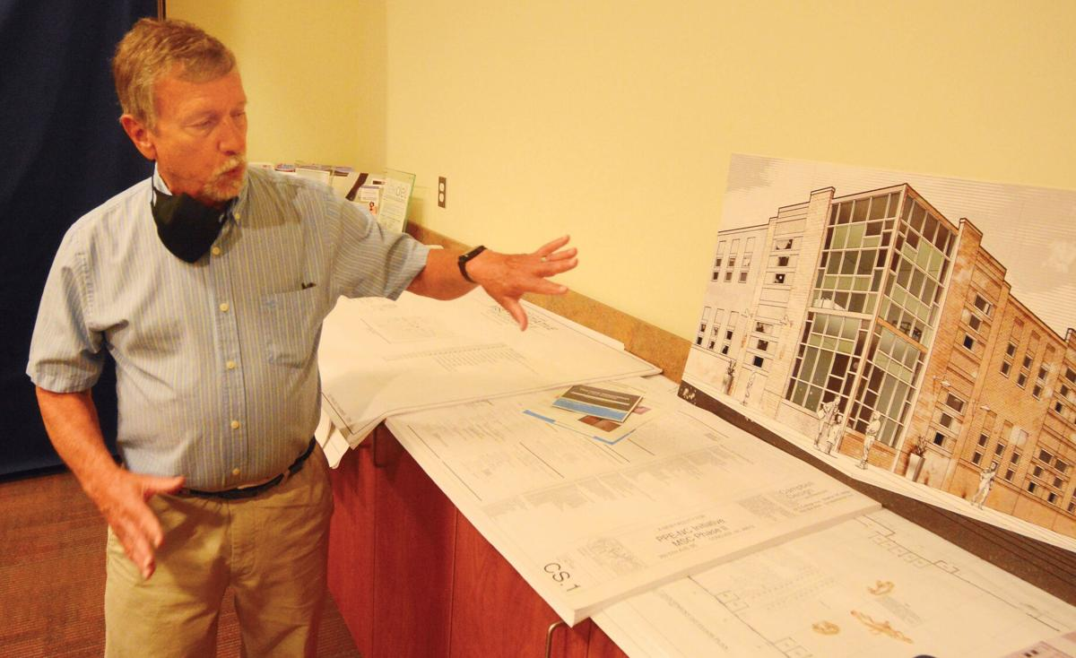 Manufacturing Solutions Center Special Projects Director Tony Whitener shows off a rendering of the new building that will be constructed near the existing building.  Photo by Robert C. Reed, Hickory Daily Record