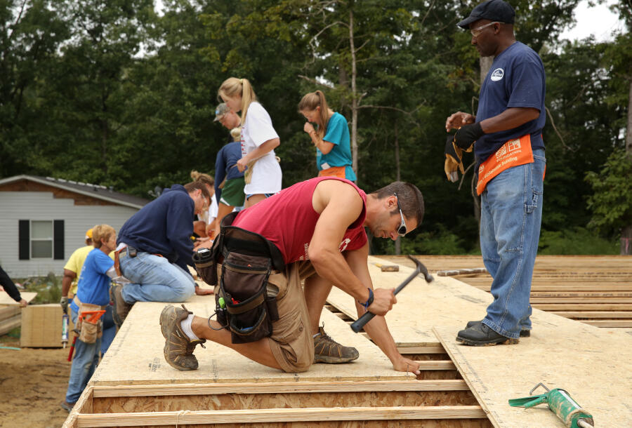 Volunteers working together to build a Habitat home