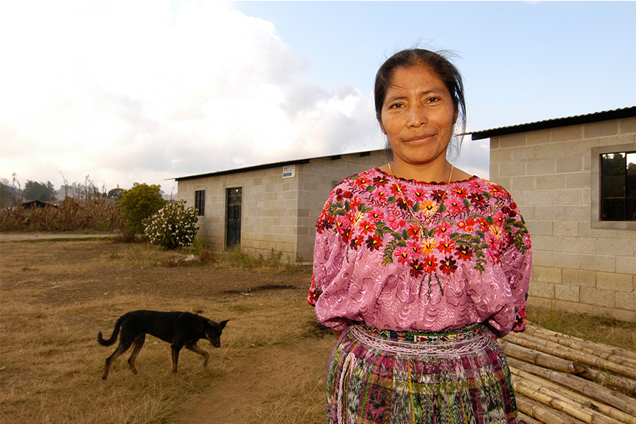 A woman stands in front of a Habitat home in Guatemala