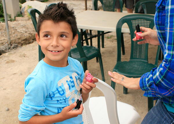 A child in Honduras paints a volunteer's nails