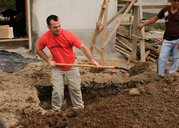 A volunteer digs a hole in Honduras
