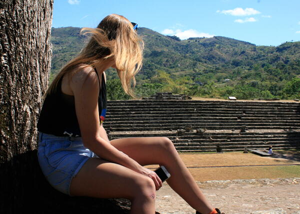 A volunteer sits in front of the Copan Ruins