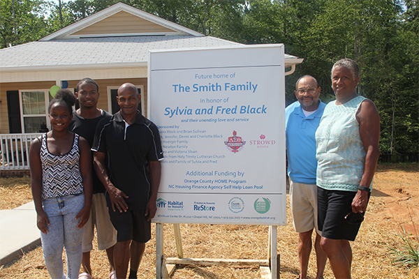 The Smith Family stand in front of their new home with Fred and Sylvia Black