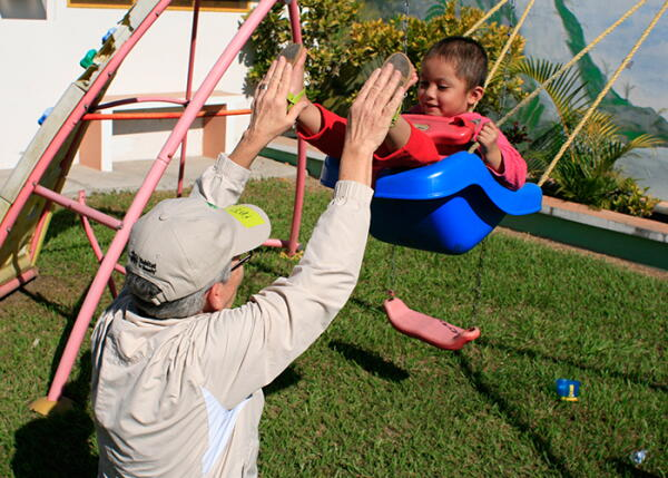 A volunteer plays with kids on the swing