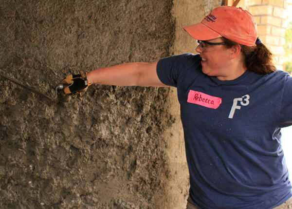 A volunteer plasters a house in Honduras