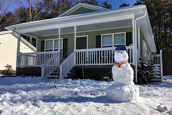A snowman stands in front of a Habitat home