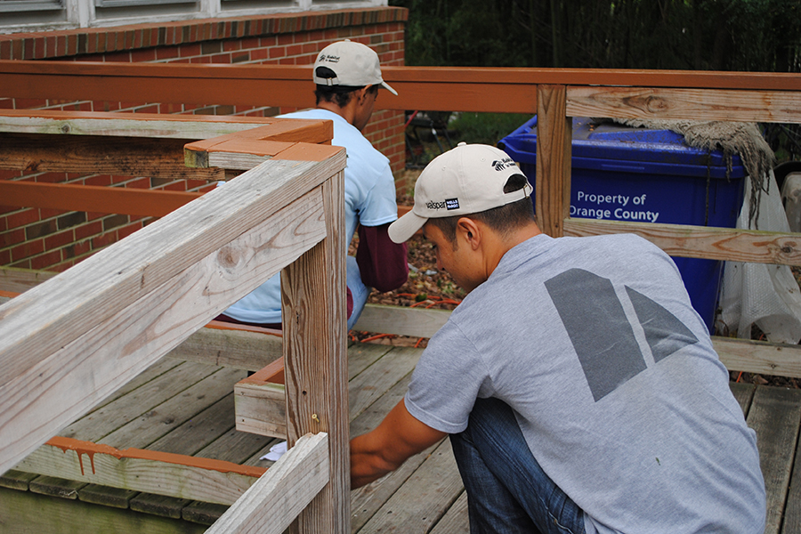 Two volunteers paint a deck.